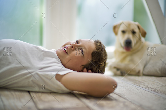 Boy lying down on a wooden floor with his pet dog nearby