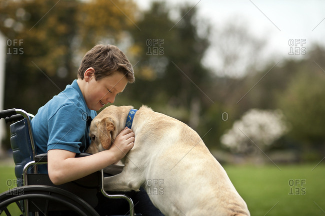 Teenage boy in a wheelchair petting his dog