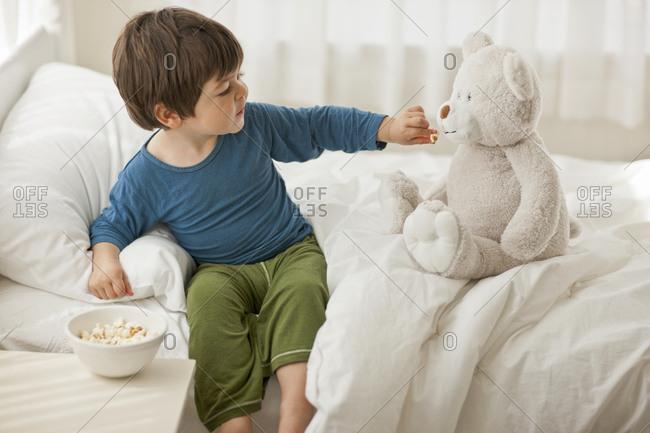 Boy feeding popcorn to his teddy bear