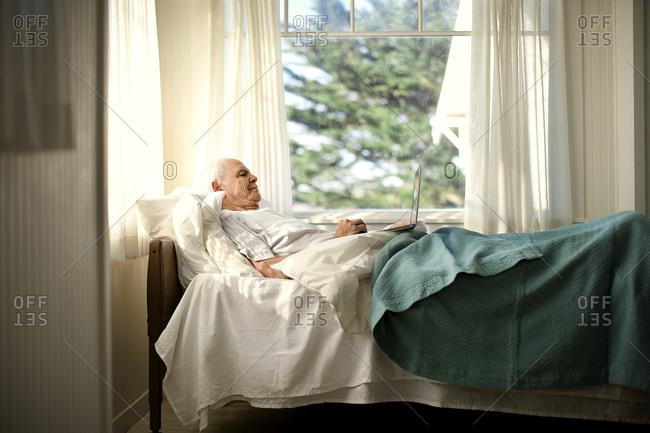 Senior man using a laptop in bed