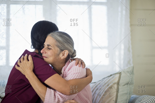 Nurse hugging a senior woman