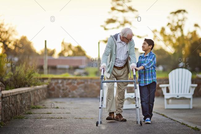 Boy with a senior man using a walking frame