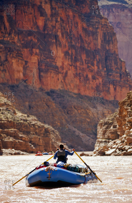 Man rowing a raft in a canyon river