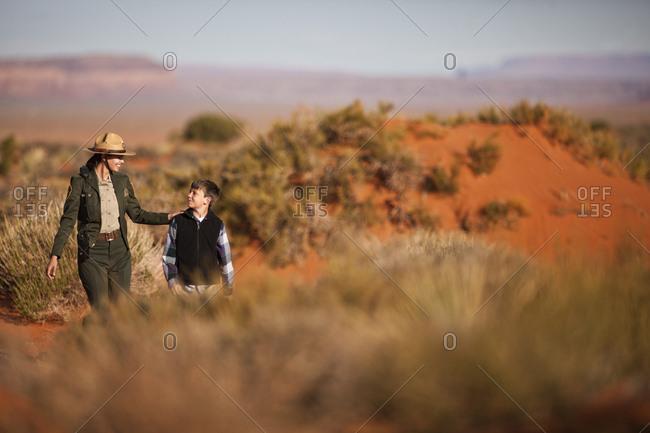 Park ranger walking with a boy in a desert