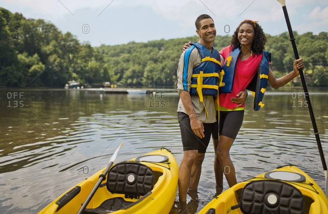 Young couple posing beside kayaks