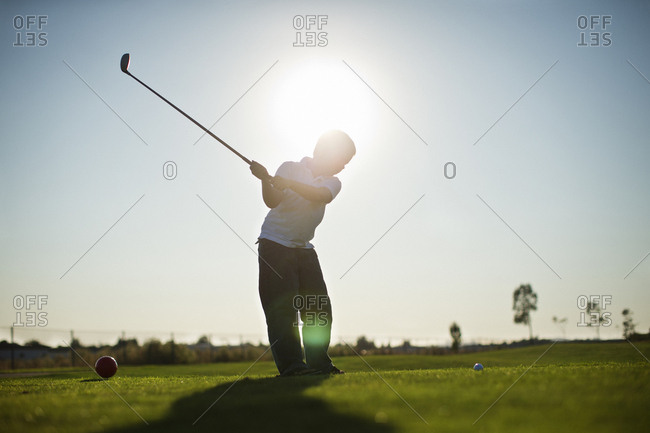 Silhouette of a boy playing golf