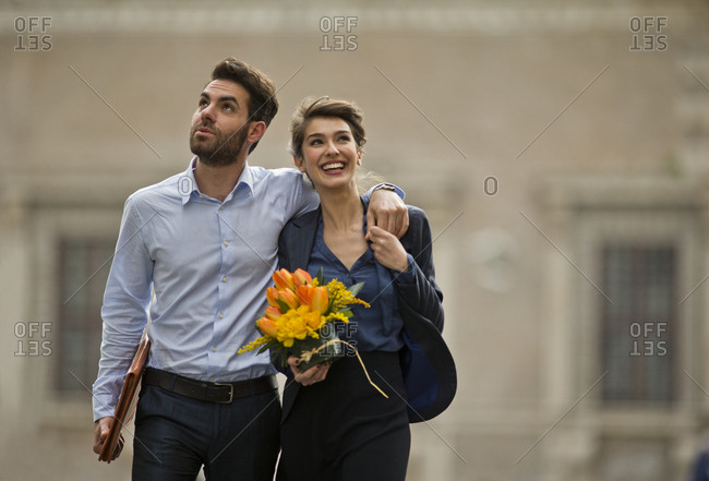 Young woman with bouquet walking with her boyfriend