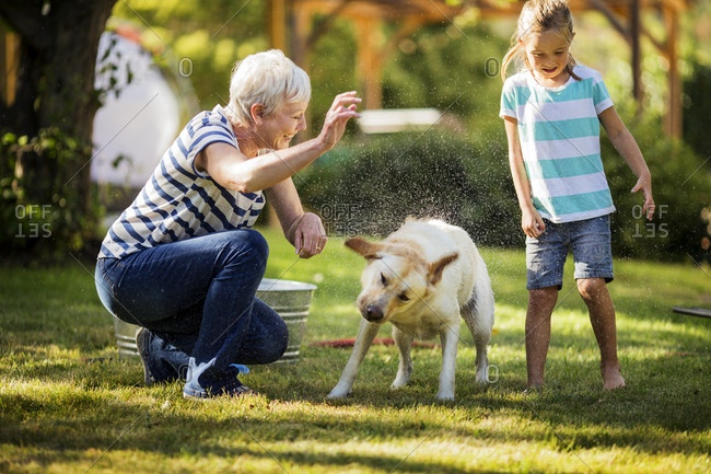 Senior woman and her granddaughter washing a dog