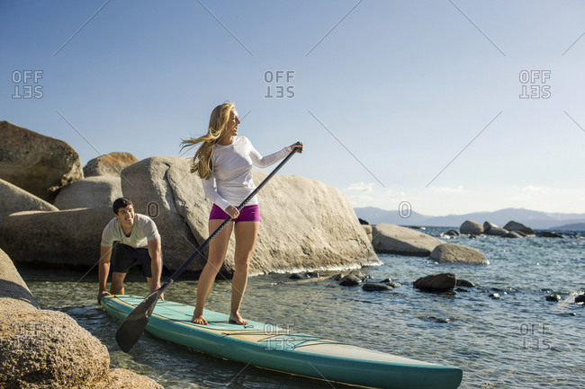 Young woman paddle boarding with her boyfriend