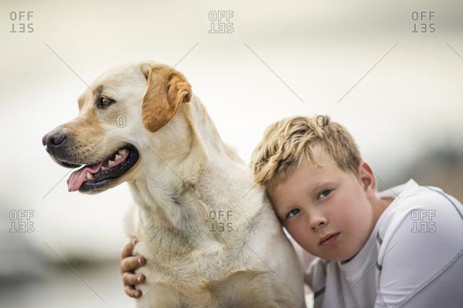 Boy with his pet yellow Labrador