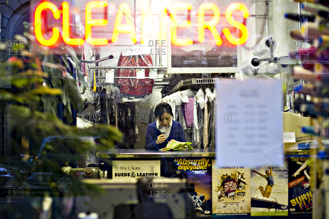New York, United States of America - October 10, 2009. An Asian lady is stitching a clothing piece inside a dry cleaner in New York City.