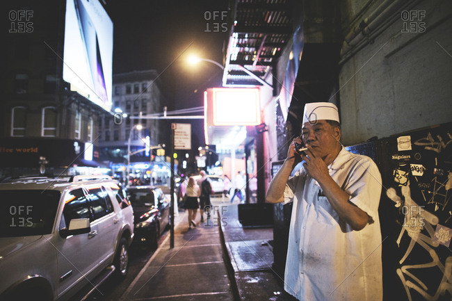 New York, United States of America - September 22, 2014. An Asian-American chef is smoking and talking on phone during a break in New York City.