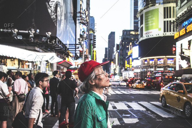 New York, United States of America - May 30, 2015. An Asian man with a red cap walks the famous Times Square in New York City.