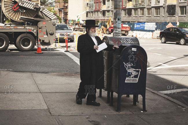 New York, United States of America - May 13, 2013. A Jewish man is sending a letter in a letter box in New York City.
