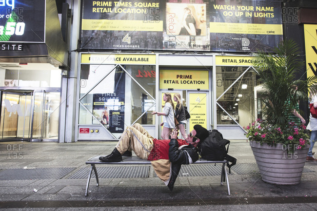 New York, United States of America - May 30, 2015. A man is dressed as Elvis Presley resting on a bench at the famous Times Square in New York City.