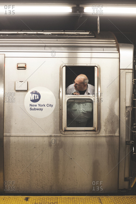 New York, United States of America - May 15, 2013. A train operator is looking out of the window from a train at the New York City Subway.