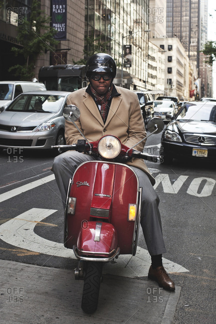 New York, United States of America - May 14, 2013.  A well dressed man on a Stella scooter seen in New York City.