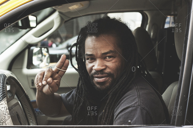 New York, United States of America - May 14, 2013. A taxi driver with dreadlocks portrayed in his cab in New York City.
