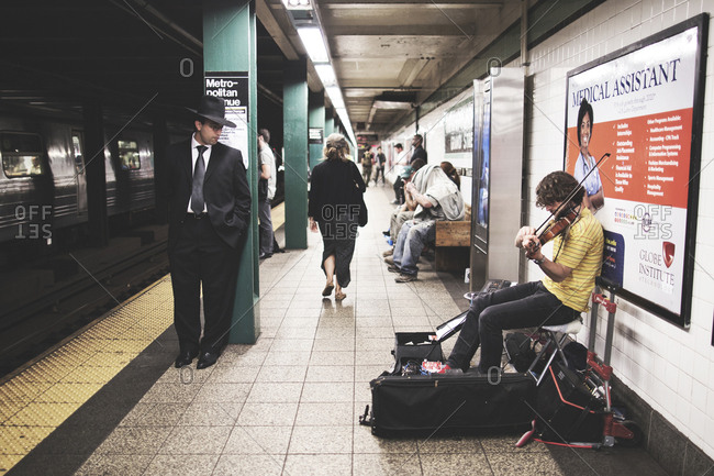 New York, United States of America - September 17, 2014. A man watching a street musician playing the Violin at a subway station in New York City.