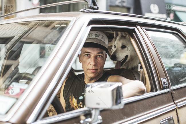New York, United States of America - May 30, 2015. A man is portrayed with his dog in his car in New York City.