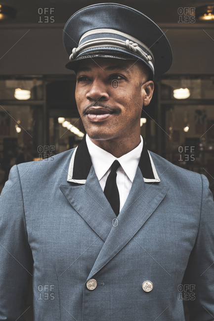 New York, United States of America - May 14, 2013. A proud and smiling doorman wears a hat and uniform at an entrance to a building in New York City.