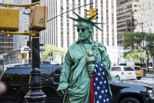 New York, United States of America - July 16, 2015. A street performer is dressed as The Statue of Liberty and seen on a street in New York City.