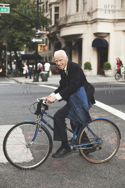New York, United States of America - May 17, 2013. Bill Cunningham on his bike in New York City.