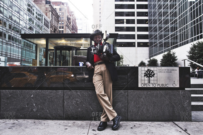 New York, United States of America - September 24, 2014. Louis Mendes, famous NYC street photographer, poses with his camera outside of the International Center of Photography school.