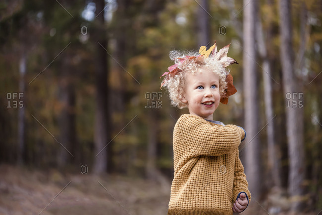 Curly-haired child with autumn leaf crown