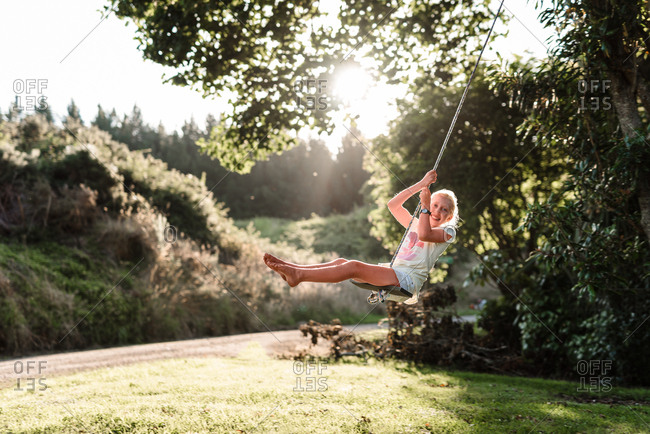 Pre-teen girl swings on a rope swing in beautiful green yard