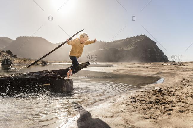Child leaping off tree stump on beach