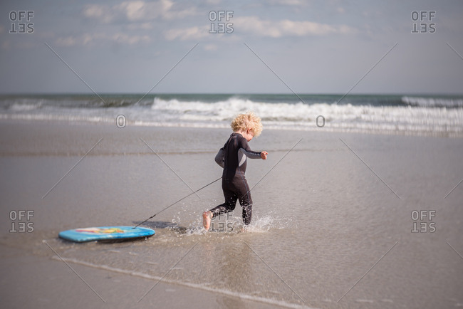 Little boy running into water with boogie board