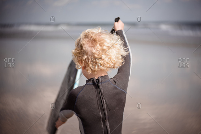 Rear view of boy with boogie board on a beach
