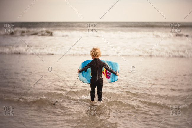 Rear view of boy with boogie board in the ocean