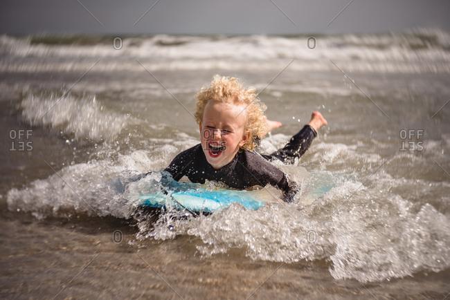 Little boy riding boogie board in the ocean