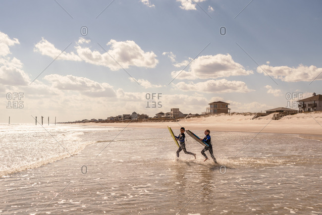 Children running into ocean waves with boogie boards