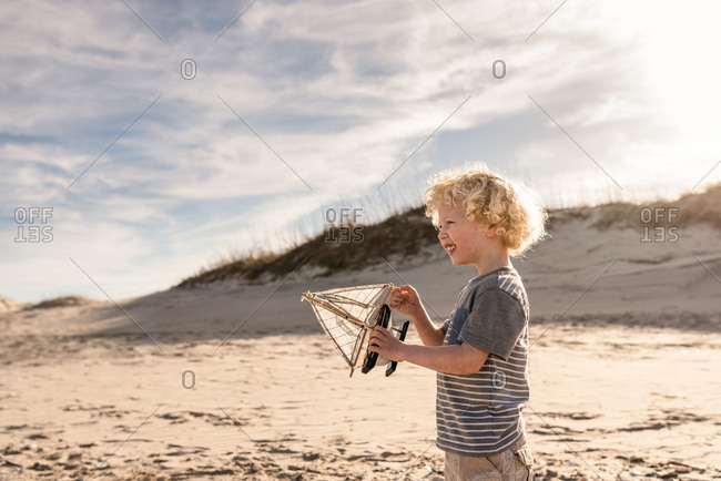 Boy playing with toy sailboat on a beach