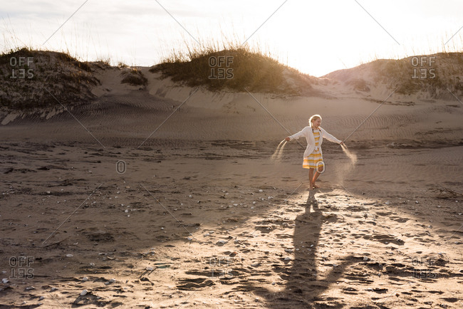 Girl tossing sand around on a beach in the Outer Banks, North Carolina