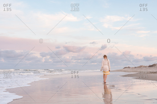 Little girl walking on ocean shore of Nags Head, North Carolina