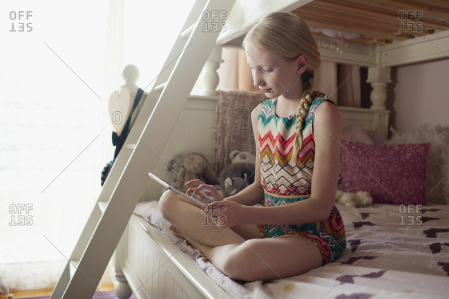 Girl using digital tablet at bedroom