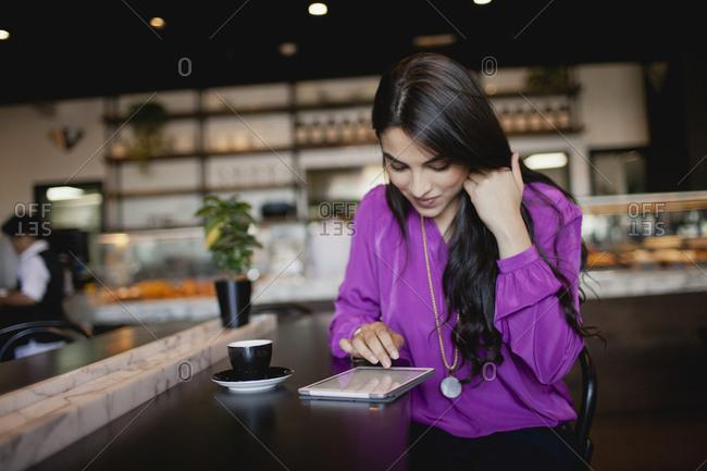 Woman using digital tablet at restaurant