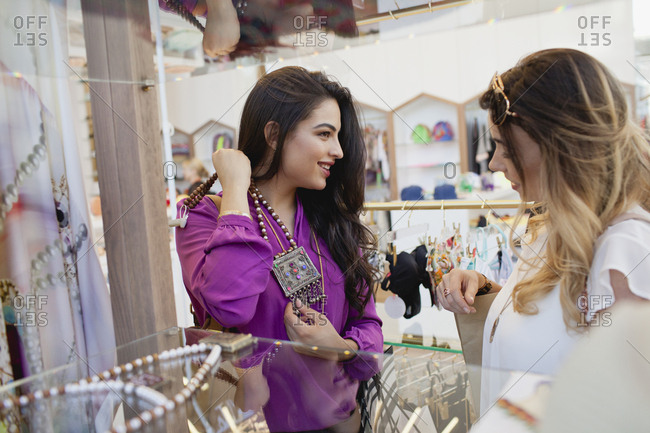 Women trying on necklace at boutique