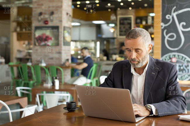 Expat businessman using laptop at cafe