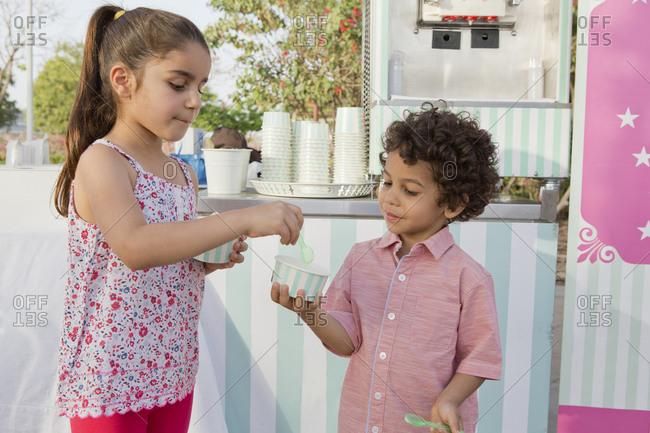 Siblings eating ice cream at park