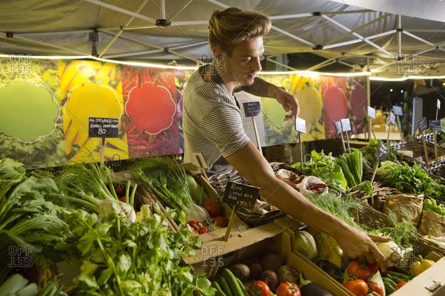 Vendor arranging vegetables at market
