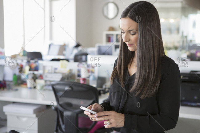 Businesswoman messaging on mobile at office