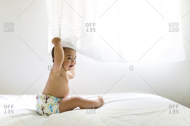 Baby girl sitting on bed playing with curtain