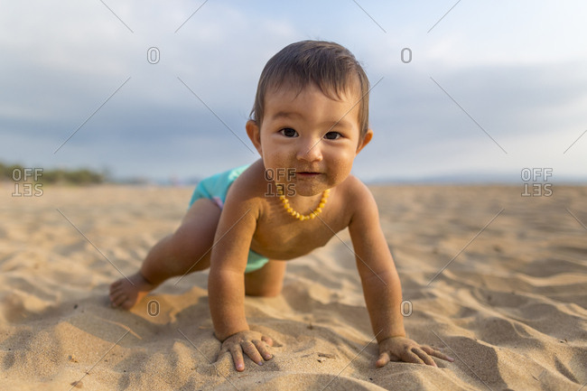 Baby girl crawling on beach with sand on face