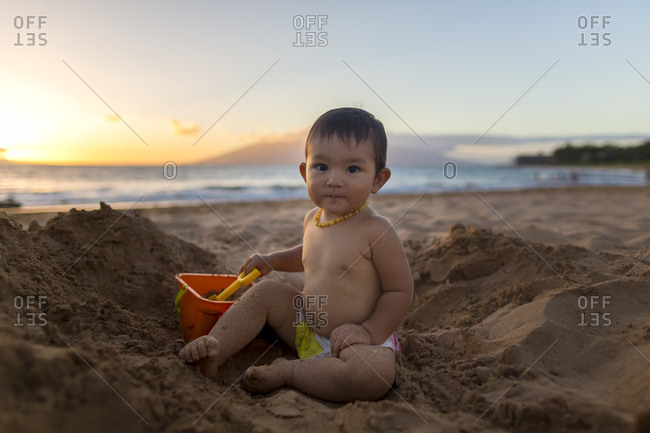 Baby girl playing in sand at the beach at sunset.
