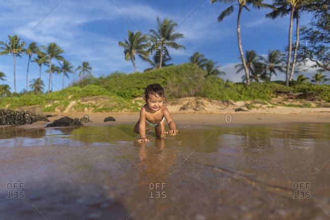 Baby girl crawling into ocean
